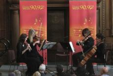 A string quartet plays on a stage in front of a Classical WETA banner