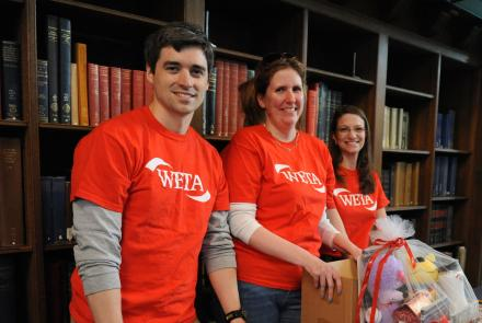 Three volunteers standing behind WETA promotions table t the Folger Shakepeare Library in Washington, D.C.