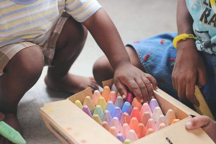 A child's hands and a box of chalk.